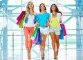 Glamorous consumers portrait of three girlfriends with paperbags after shopping in trade center Royalty Free Stock Photo