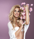 Glamorous curvy blonde woman with a sexy body posing with flowers on a pink studio background Stock Photo