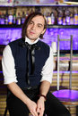 Glamorous man sits near bar counter in black vest and white shirt Royalty Free Stock Photo