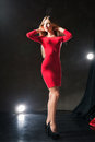 Glamorous smiling young woman standing on stage wearing red dress and touching her neck Stock Image