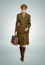 Glamorous woman in military uniform a stylish brown walking towards the camera carring an attache case over grey Royalty Free Stock Image