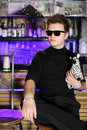 Glamorous young man sits near bar counter in black and sunglasses Stock Photos