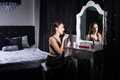 Glamorous young woman applying makeup in front of the mirror in an elegant bedroom in shadowed light Stock Images