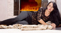 Glamorous young woman lacy black top slacks lying fur coat front fire resting her elbow looking camera Stock Images