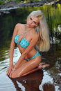 Glamour blond model with sexy body in blue bikini posing pretty at the nature location Royalty Free Stock Photo