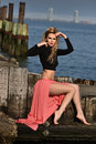 Glamour fashion model posing on the pier at boat marina with water on the background in black top and pink maxi skirt Royalty Free Stock Photography