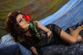 Glamour girl holding red rose is lying down and Royalty Free Stock Photography