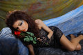 Glamour girl holding red rose sad is lying down and Stock Photo