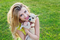 Glamour happy smiling girl or woman holding cute chihuahua puppy dog on green lawn on the sunset