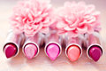 Glamour lipsticks and flower petals Royalty Free Stock Photography