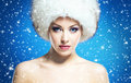 Glamour portrait of a young and beautiful woman in a winter hat on blue background with falling snowflakes Stock Images