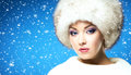 Glamour portrait of a young and beautiful woman in a winter hat over blue background with falling snowflakes Stock Photography
