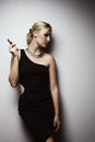 Glamour smoke a blondy woman in black dress with cigar near wall Royalty Free Stock Images