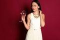 Glamour woman with long dark hair wears elegant dress with bijou,