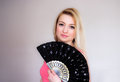 Glance peaceful blond woman holding a fan Royalty Free Stock Photo