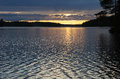 The glare of sunset covered light ripples lake Stock Photo