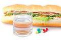Glas water pillen en twee hotdogs met diverse ingrediënten Royalty-vrije Stock Afbeelding