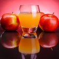 Glass of apple juice with apples on a red background Stock Photography