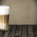 Glass of aromatic macchiato italian coffee with rich full roast espresso topped with foamy milk and served on a rustic wooden Royalty Free Stock Photo