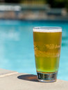 Glass of beer on edge by poolside Royalty Free Stock Photo