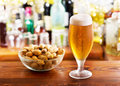 Glass of beer with peanuts Royalty Free Stock Photo