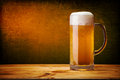 Glass of beer on wood table with grunge wall Royalty Free Stock Photography
