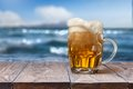 Glass of beer on wooden table with sea on background Royalty Free Stock Photo