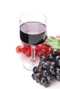 Glass of black wine and grapes on white background Royalty Free Stock Photos