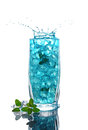 Glass of a blue alcoholic cocktail drink with ice and mint Royalty Free Stock Photo