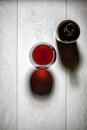 Glass and bottle of red wine with cork on table Royalty Free Stock Photo