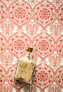 Glass bottle with sand on patterned background vintage pattern Stock Image