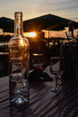 Glass bottle at sunset and wine glasses in the on the table Royalty Free Stock Photos