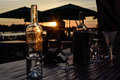 Glass bottle at sunset and wine glasses in the on the table Royalty Free Stock Photo