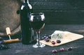 Glass and bottle of wine on a wooden barrel. Burnt, black wooden background. Vintage. Copyspace for a text. Grapes and green vine. Royalty Free Stock Photo