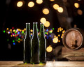 Glass bottles of beer and wooden barrel on bar lights background Royalty Free Stock Photo
