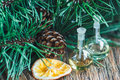 Glass bottles of essential oil with pine cones, oranges and fir branches on wooden background Royalty Free Stock Photo