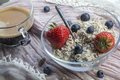 Glass bowl with old teaspoon, cereals, strawberries and blueberries Royalty Free Stock Photo