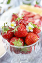 Glass bowl of strawberries standing on rustic wooden table in th the garden Stock Photo