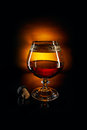 Glass of brandy and cork on black background Royalty Free Stock Photos