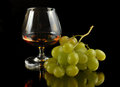 Glass of brandy and grapes on black with reflection Stock Photo