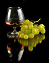 Glass of brandy and grapes on black with reflection Royalty Free Stock Image