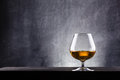Glass of brandy over a dark textured wooden background Stock Photography