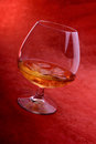 Glass of brandy with stem containing a measure on a pale red background Stock Image