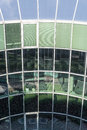 Glass building facade reflecting plants and blue sky Royalty Free Stock Photo