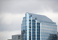 Glass building reflective against a cloudy gray sky Stock Photography