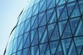 Glass building side of a blue circular shaped office Royalty Free Stock Images