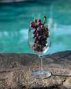 Glass of cabernet a grapes sit in a poolside Stock Photos