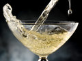 Glass of champagne poured in rivers to celebrate Royalty Free Stock Image