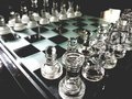 A glass chess board with pieces. Royalty Free Stock Photo