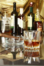 Glass of cognac, brandy or whiscy on mirror table. bottles in a bar on the background Royalty Free Stock Photo